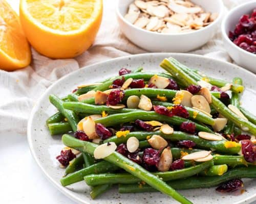 green beans with garlic, dried cranberries, almonds and orange zest on plate with orange and almonds in background