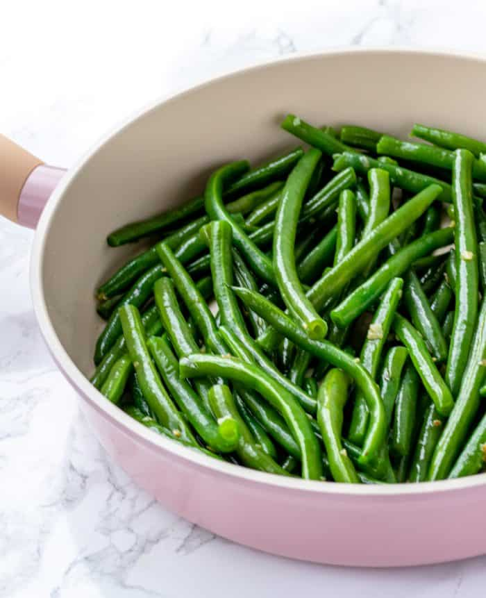 green beans with garlic and olive oil being sauteed in a pan
