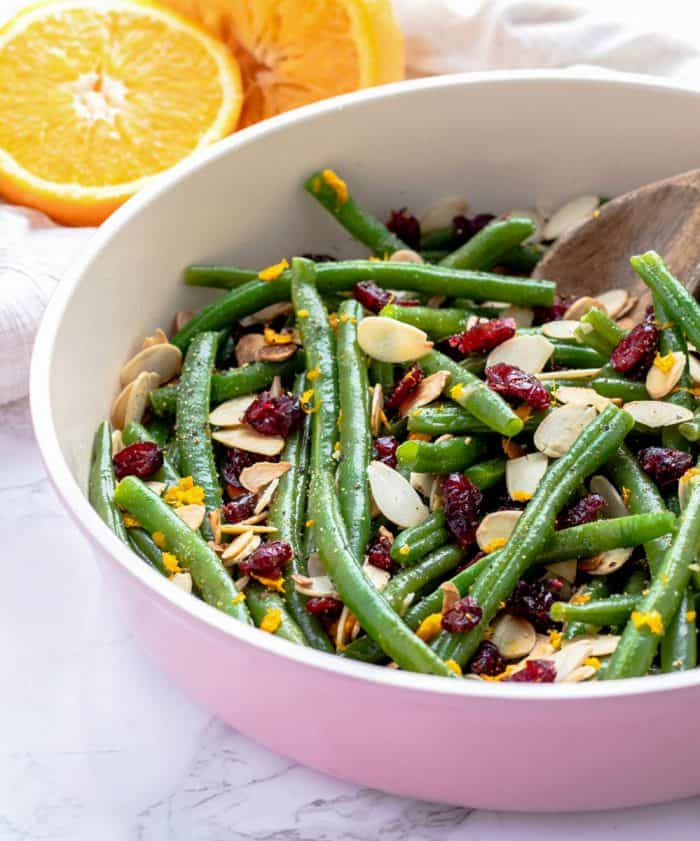green beans with garlic, dried cranberries, almonds and orange zest in a large pan with a rustic wooden spoon next to fresh orange halves
