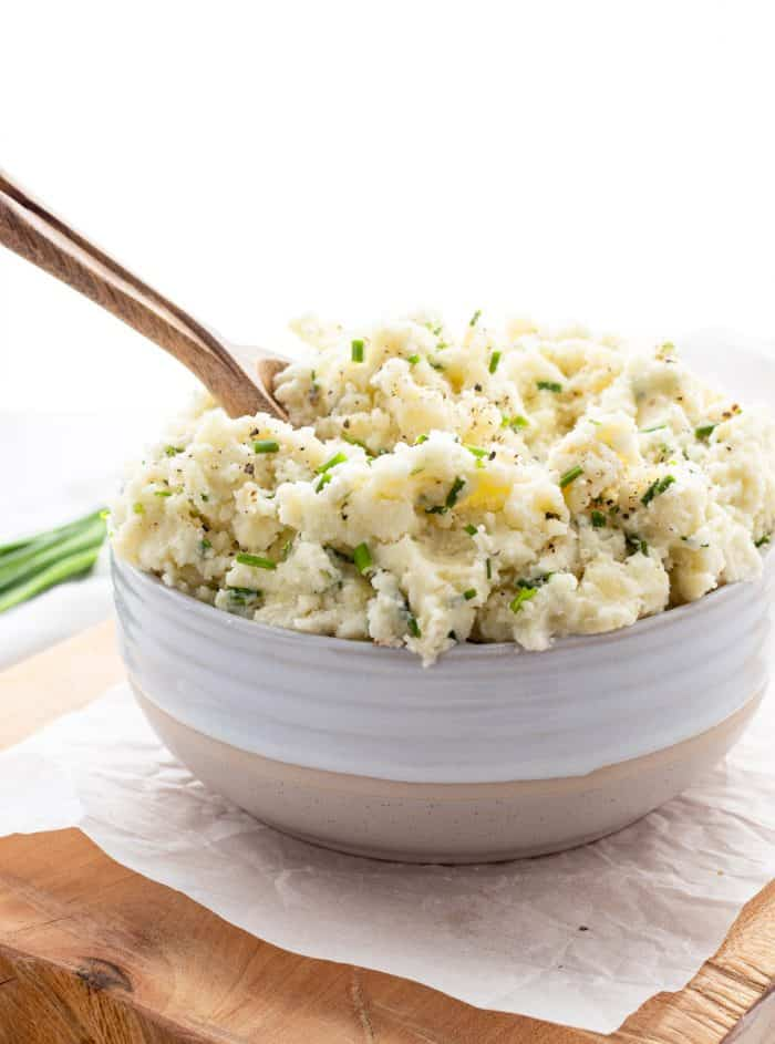Mashed potatoes served in a white bowl with wooden spoon.