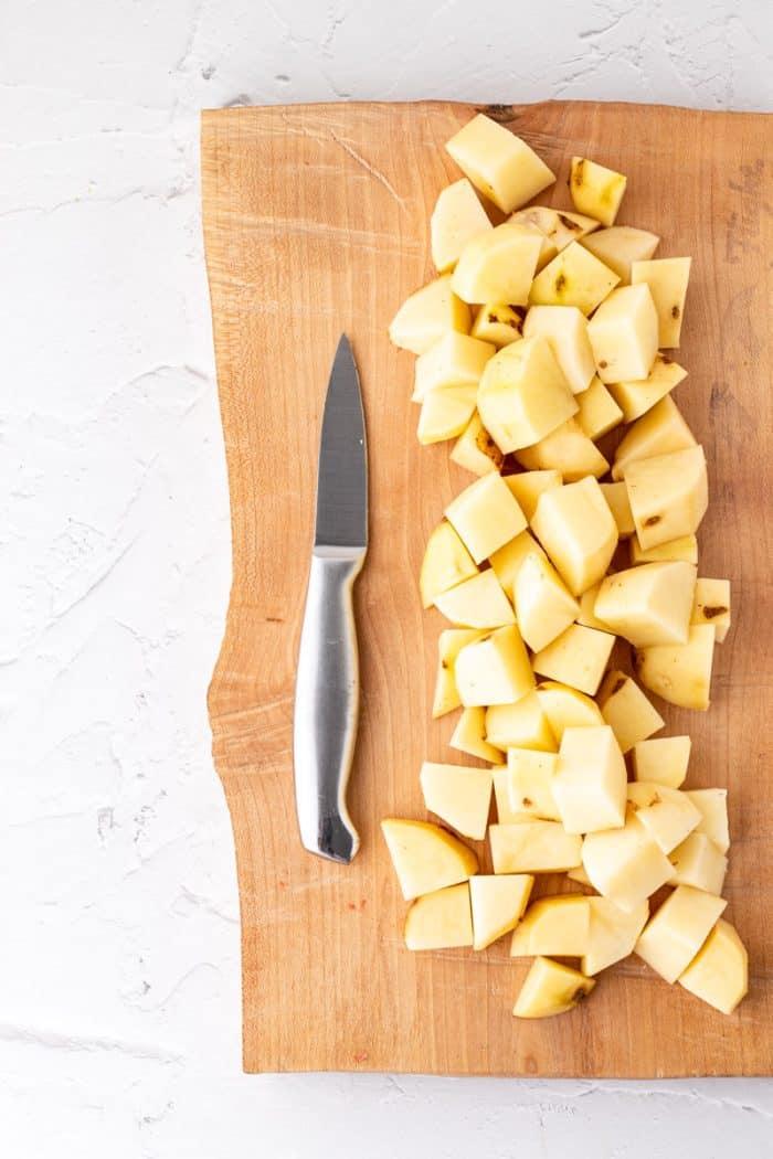 Cut potatoes on a wooden chopping board.