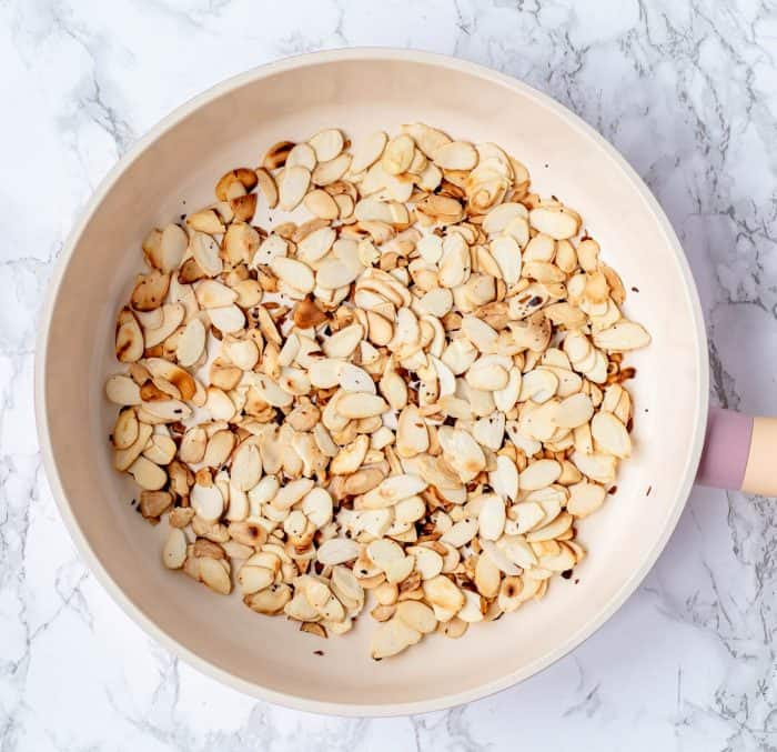 sliced almonds toasting in a large frying pan on marble background