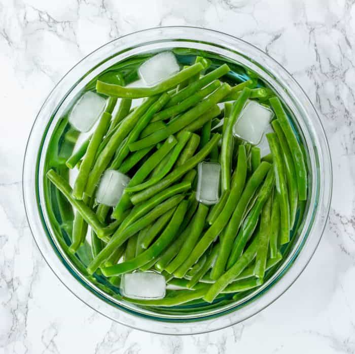 green beans chilling in bowl of ice water on marble background