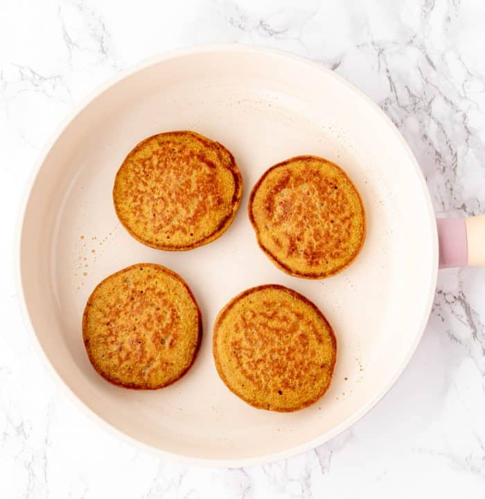 cooked pumpkin pancakes in a white frying pan