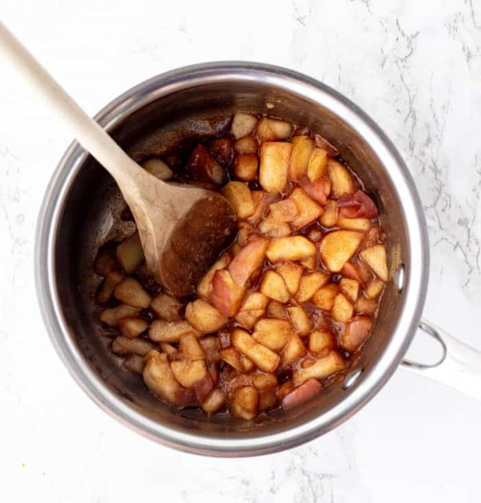 apple topping for pancakes in a pot with a wooden spoon