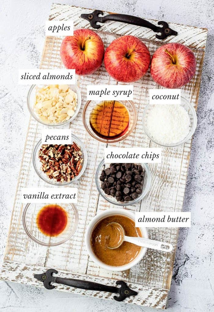 ingredients for apple nachos on a rustic wooden board with labels