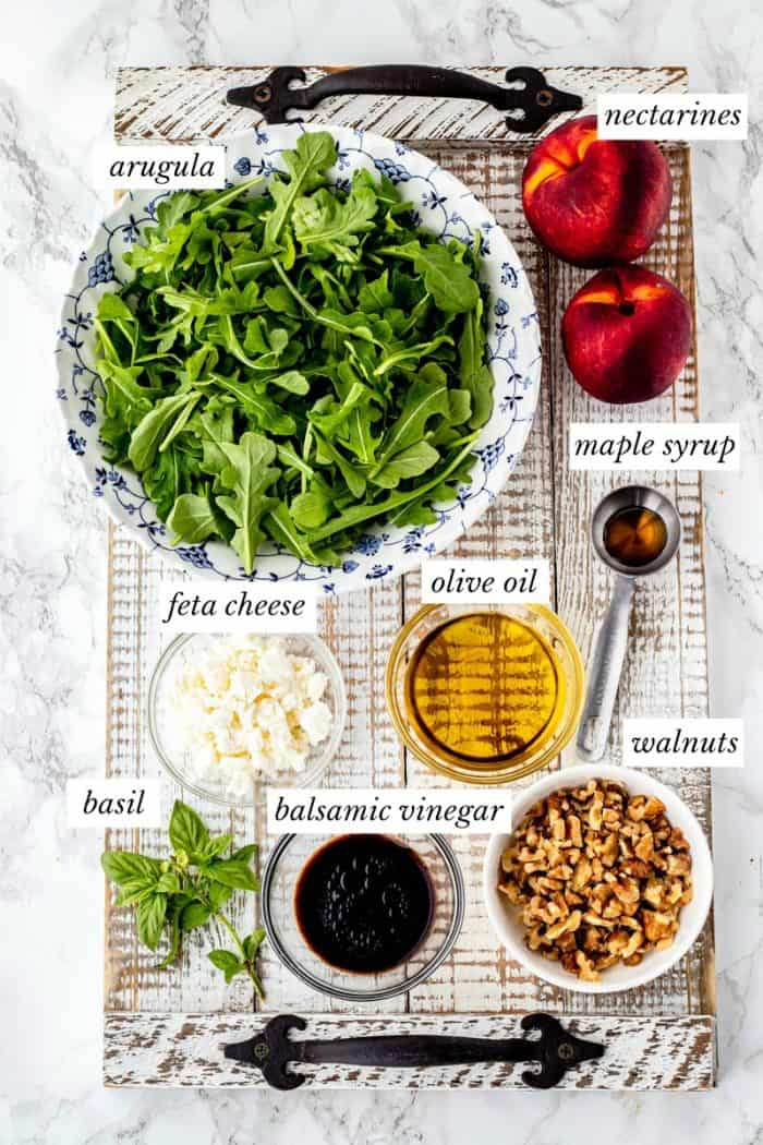 ingredients with labels for nectarine salad on a rustic wooden tray