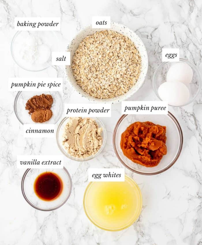 ingredients for pumpkin protein pancakes on marble background with labels