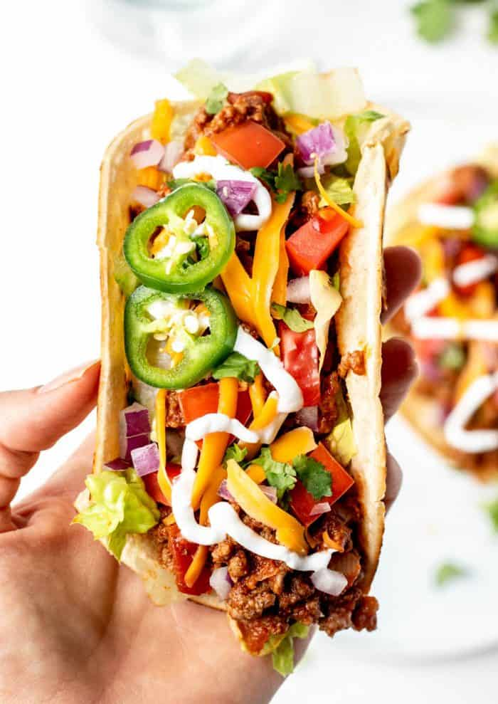Overhead shot of a hand holding a Crock Pot taco meat taco with fresh toppings.