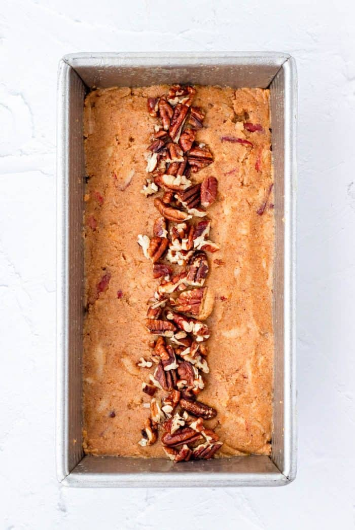 Pumpkin loaf batter in a loaf pan topped with pecans