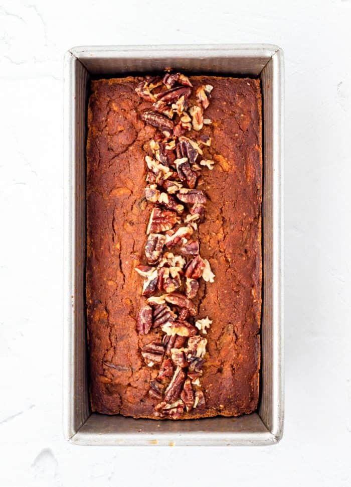 Baked pumpkin bread in a loaf pan topped with pecans