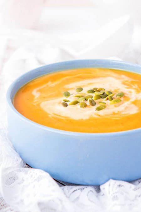 Butternut squash soup served in a blue bowl and topped with pumpkin seeds and coconut cream.