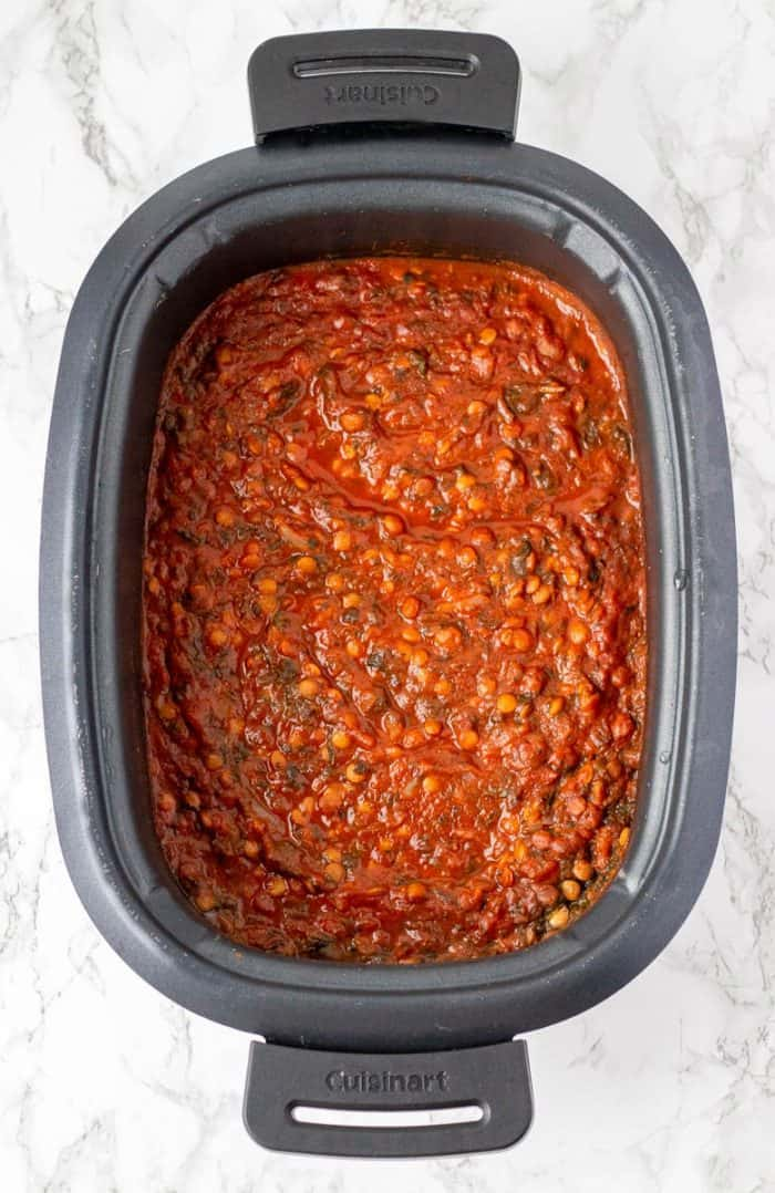 Cooked lentil bolognese sauce in crockpot on marble background