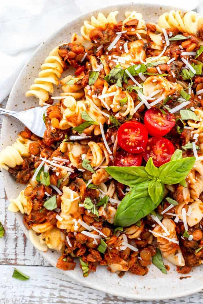 Top down shot of plate filled with lentil bolognese on bed of pasta garnished with fresh basil and tomatoes with a fork digging in