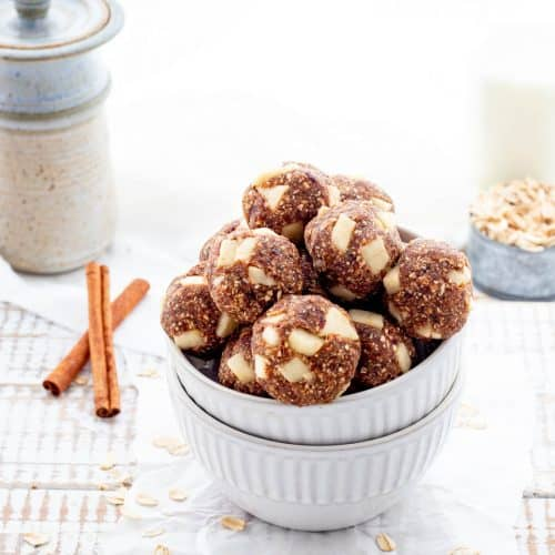 Bowl of energy balls with oats, cinnamon sticks and jug of milk on rustic white board
