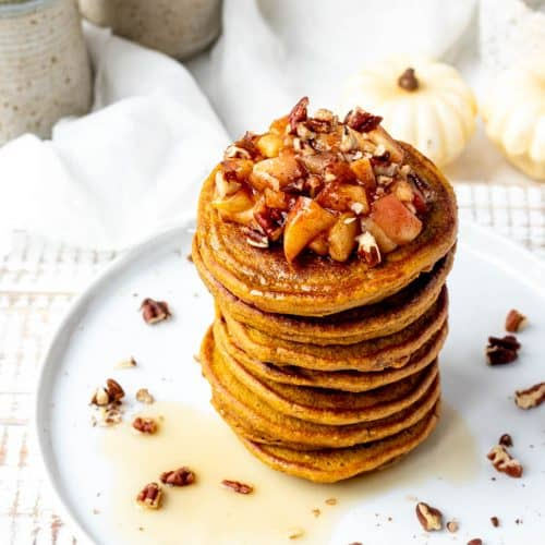 stack of pumpkin pancakes on white plate with a sprinkle of pecans and apple topping with white pumpkins in background