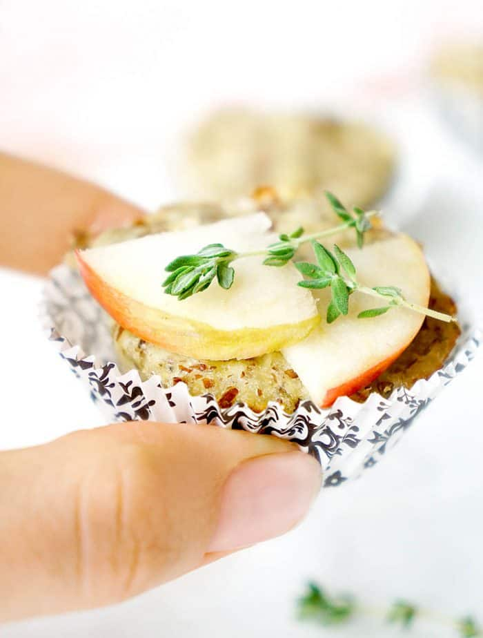 Holding turkey muffin with apple slices and thyme on top