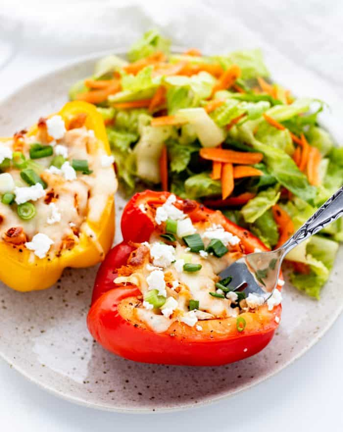 A fork digging into a chicken stuffed pepper with a side salad