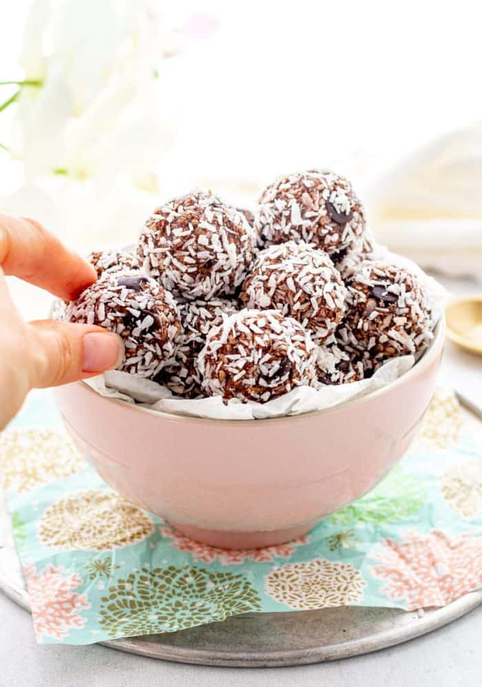 A hand taking one of the chocolate coconut balls out of a bowl.