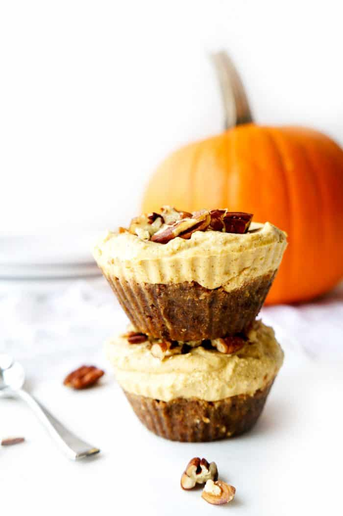 two vegan cheesecake bites stacked with pumpkin in background