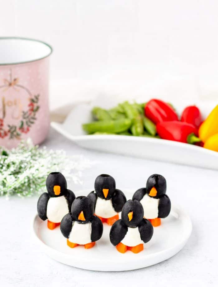 Five olive penguins on a white plate.