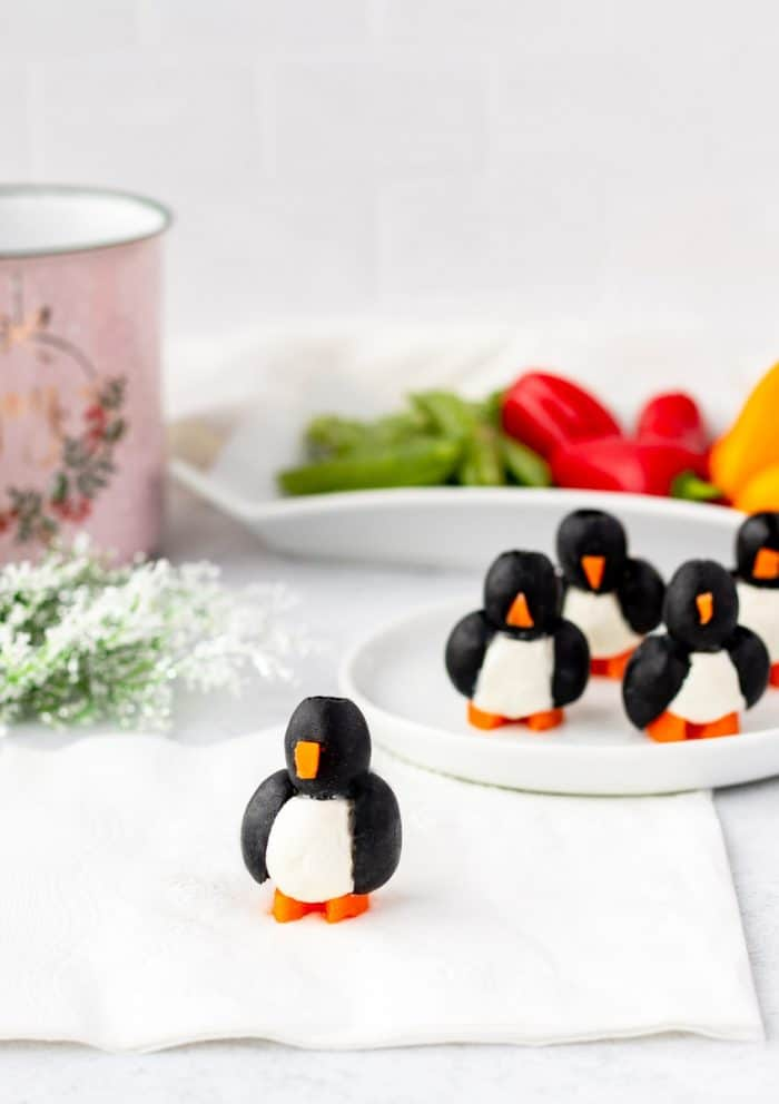 Four penguin appetizers on a plate with one in front on a napkin.