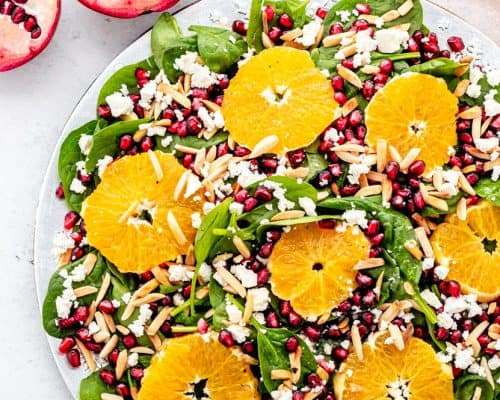 Spinach salad topped with pomegranate and sliced orange.