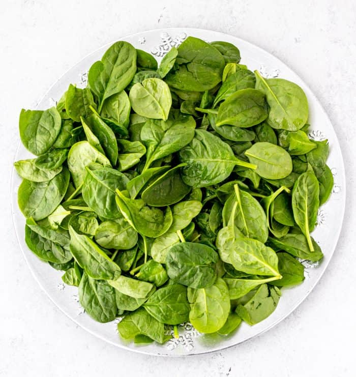 Babay spinach leaves on a white plate.