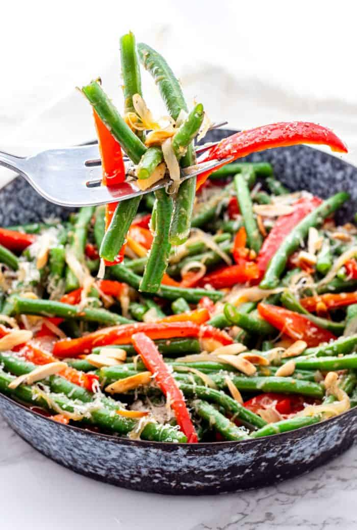 A fork picking up green beans and red pepper slices.