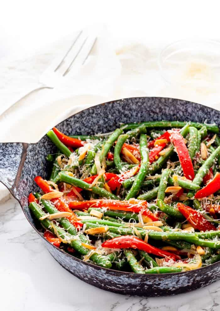 Sauteed green beans and red peppers in a skillet.