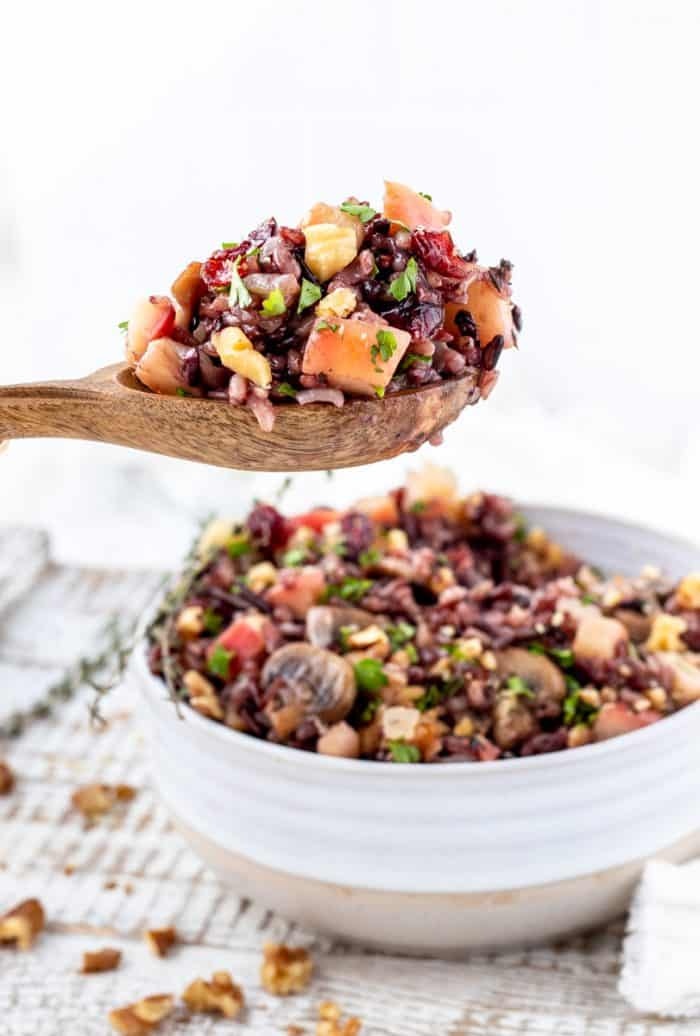 The wild rice pilaf on a wooden spoon being served.