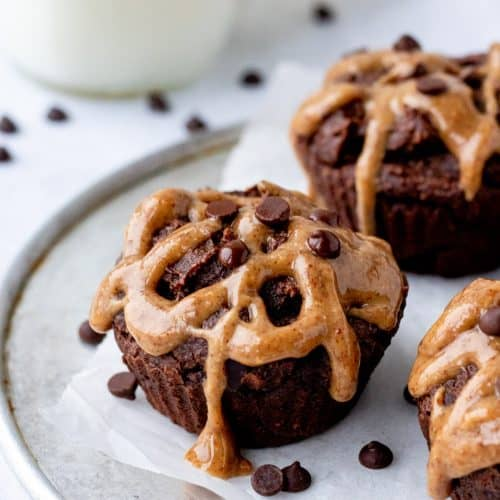 close up of brownies on a tray with chocolate chips and almond butter frosting