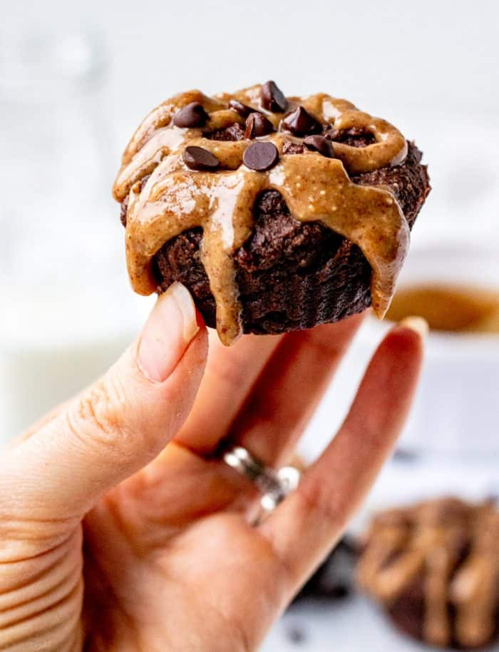 holding a brownie with almond butter drizzle