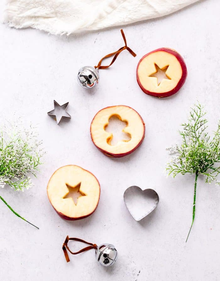stars and gingerbread man cut out of apple slices with cookie cutters with greenery and cookie cutters surrounding them