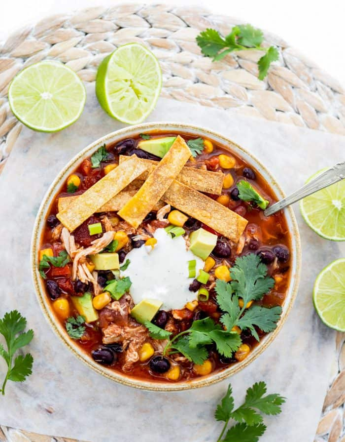 bowl of chicken tortilla soup with spoon topped with crispy tortilla strips with limes next to it