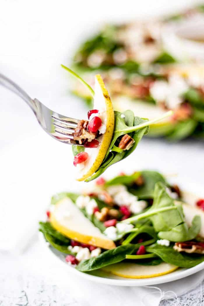 spinach salad with pomegranates, pears and pecans on a fork