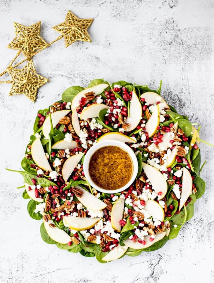 christmas wreath salad with golden stars next to it