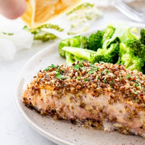 A fillet of baked salmon served in a plate with broccoli.