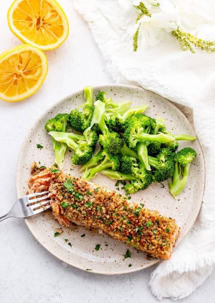 A fork cutting into a fillet of walnut crusted salmon.