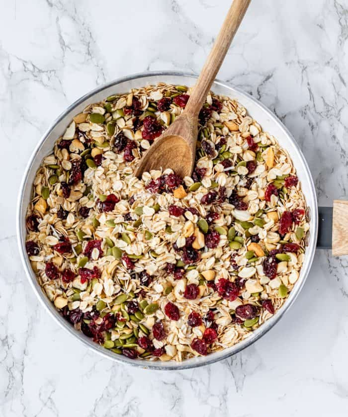 oats, pumpkin seeds, dried cranberries and coconut in frying pan with wooden spoon