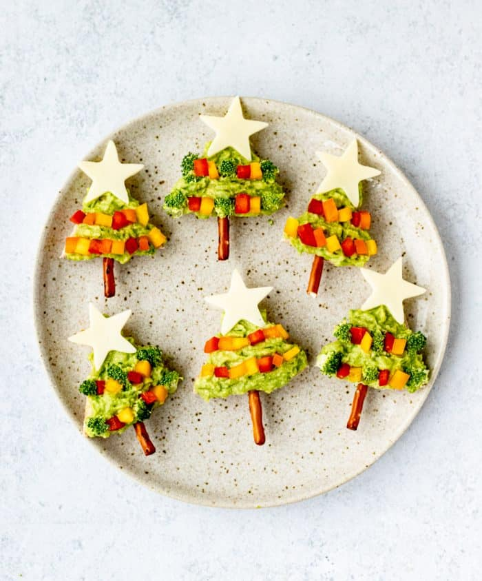 avocado pita christmas trees on a plate with cheese stars and pretzel trunks