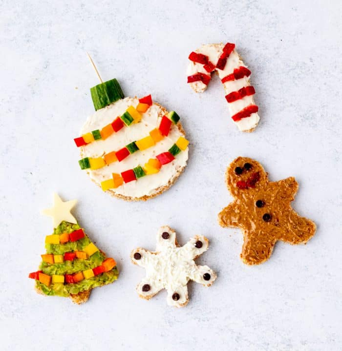 Christmas tree, candy cane, ornament, snowflake and gingerbread man cut out of toast and decorated with fruits, veggies and chocolate chips