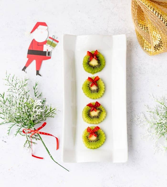 kiwi wreaths on a white platter next to Santa and greenery