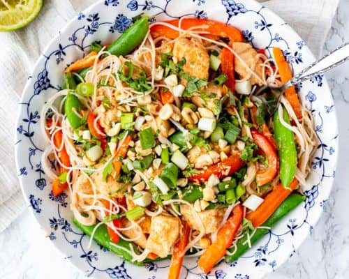 peanut chicken mixed with vegetables and rice noodles in a bowl with limes and peanuts
