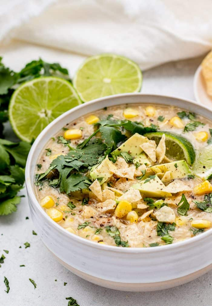 White chicken chili topped with a lime slice and fresh cilantro.