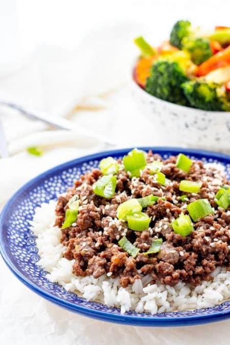 Korean ground beef next to a bowl of steamed vegetables.