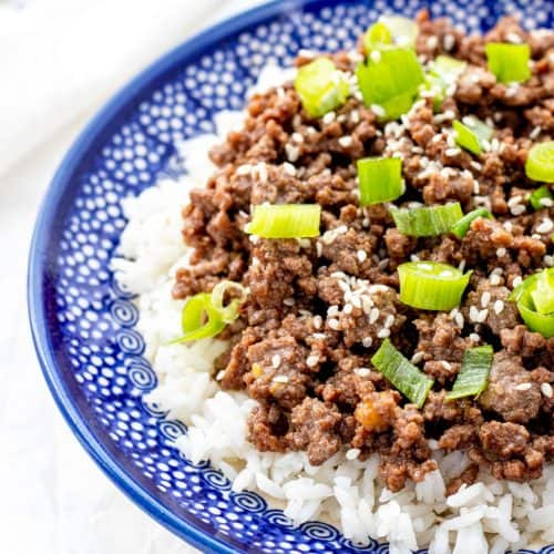 The cooked beef served on top of white rice and garnished with green onions and sesame seeds.