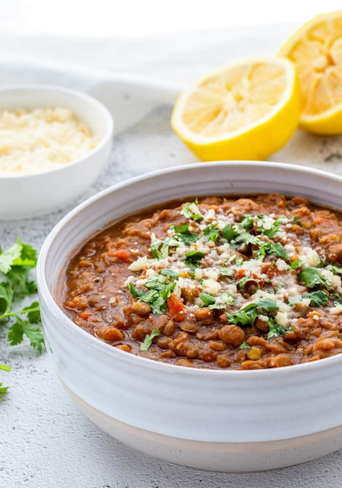 A bowl of lentil soup with fresh lemons behind it.