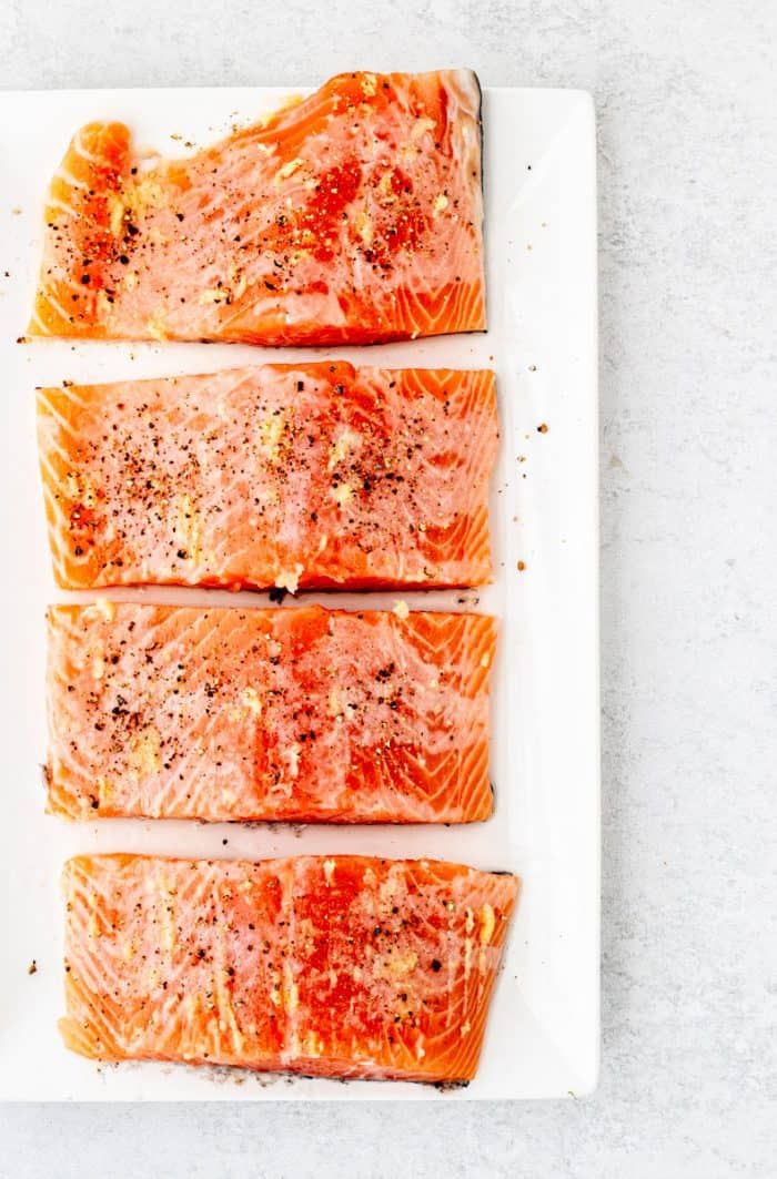Four seasoned salmon fillets on a white plate.