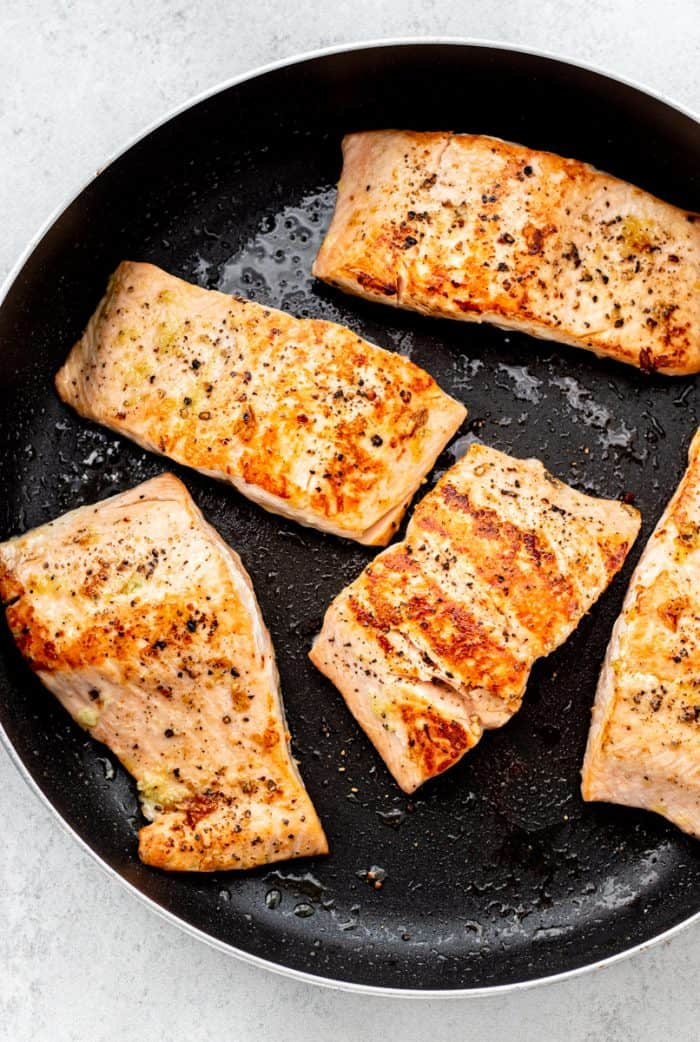 Cooked salmon fillets in a skillet.